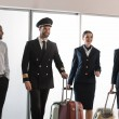 Happy aviation personnel team walking by airport l...