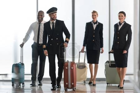 young aviation personnel team walking by airport loggy with suitcases