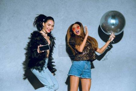 Photo pour Femmes multiethniques à la mode avec smartphone et ballon s'amuser ensemble à la fête - image libre de droit