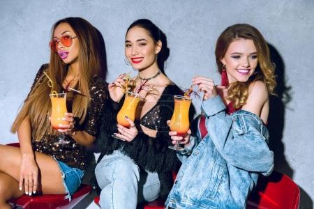 Photo pour Belles femmes multiethniques de jeunes élégantes, boire des cocktails à parti - image libre de droit