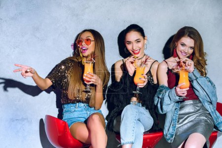 happy stylish multiethnic girls sitting on bar stools and drinking cocktails at party