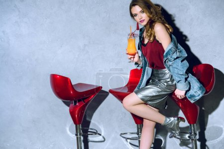 Photo pour Belle fille à la mode tenant le verre à cocktail et regarder la caméra - image libre de droit