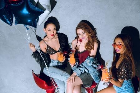 Photo pour Vue grand angle de filles multiethniques souriantes à la mode avec des ballons boire des cocktails à la fête - image libre de droit