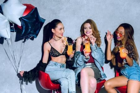 Photo pour Mode souriant filles multiethniques avec des ballons boire des cocktails à la fête - image libre de droit