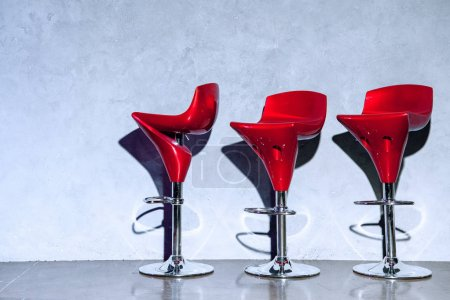 three red empty bar stools near grey wall