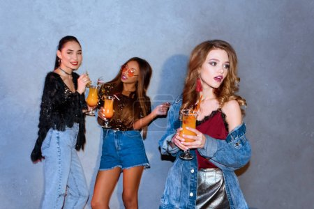 stylish young multi ethnic women holding glasses with cocktails at party