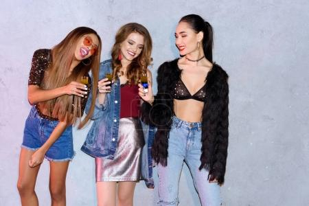 fashionable smiling young multiethnic women holding glasses with cocktails at party