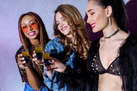 Photo pour Belles filles souriantes élégantes multiethniques tenant des lunettes avec des cocktails à la fête - image libre de droit