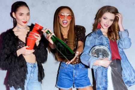 Photo pour Bouteille de vin chic jeunes femmes multiethniques avec gobelets en papier, boule disco, souriant à la caméra - image libre de droit