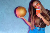 portrait of african american woman with disposable cup and golden basketball ball