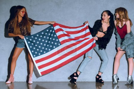 multicultural young women with american flag against concrete wall