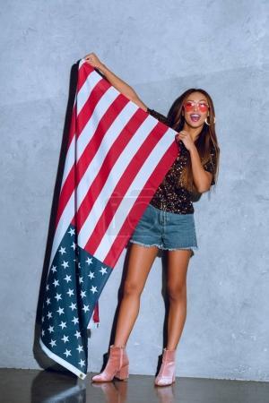 bonne humeur femme afro-américaine, tenant le drapeau américain en mains