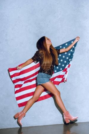 happy african american woman with american flag in hands