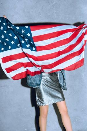 partial view of woman holding american flag against concrete wall