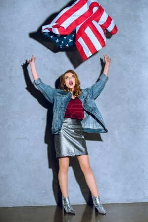 excited woman throwing american flag against concrete wall