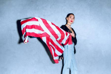 portrait of beautiful asian woman with american flag against concrete wall