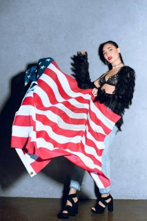 beautiful asian woman with american flag posing against concrete wall