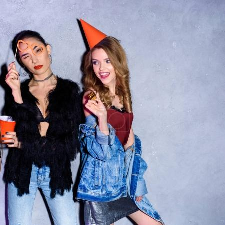 portrait of stylish multicultural women with party decorations against concrete wall