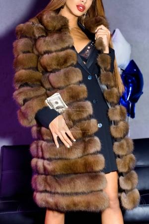 partial view of stylish woman with dollars in pocket
