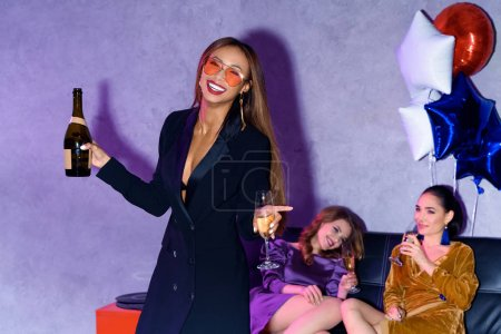 selective focus of african american woman with champagne and multicultural friends behind having party