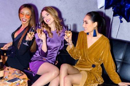 Foto de Amigos multiétnicos tintineando copas de champán durante la fiesta - Imagen libre de derechos
