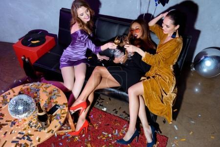 Photo pour Multiculturelles jeunes femmes cliquetis verres de champagne tout en faisant la fête ensemble - image libre de droit