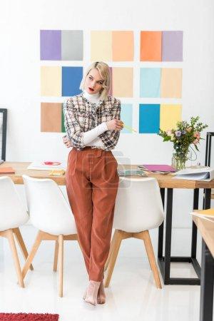 beautiful fashion magazine editor with colors palette on wall in office
