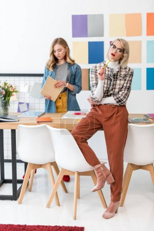 fashionable magazine editors doing paperwork at workspace with color palette