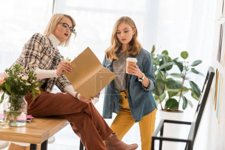 fashionable magazine editors working with documents and drinking coffee