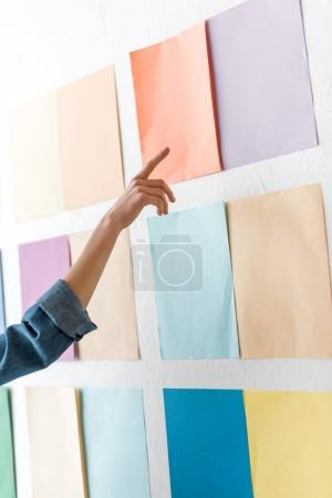 cropped view of magazine editor pointing at color palette