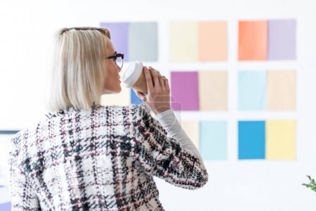 attractive fashion magazine editor drinking coffee and looking at color palette on wall