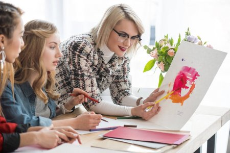 fashionable magazine editors working with sketches in modern office