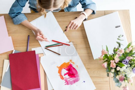 overhead view of magazine editor drawing sketches at workplace