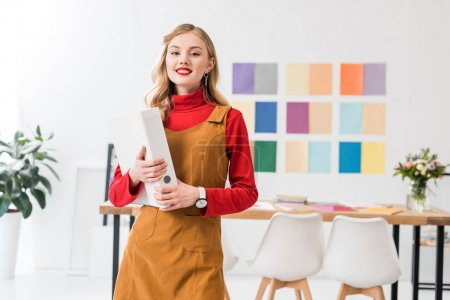 beautiful magazine editor with folder in office with color palette on wall behind