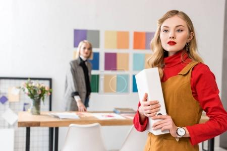 Photo for Fashion magazine editor with folder in modern office with colleague and color palette on wall behind - Royalty Free Image