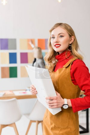 attractive magazine editor with folder in modern office with colleague and color palette on wall behind