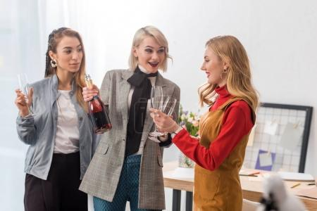 excited magazine editors celebrating with champagne in modern office