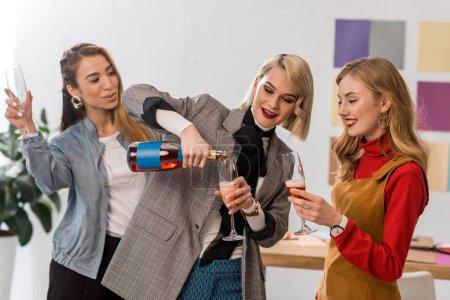 successful multiethnic magazine editors celebrating with champagne in modern office