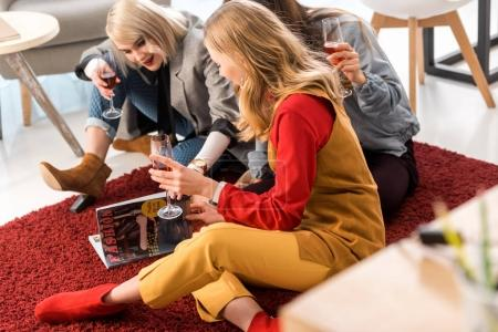 successful businesswomen celebrating with champagne and looking at magazine in modern office