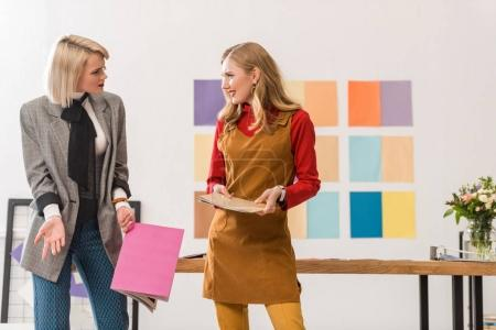 fashionable magazine editors working in modern office with color palette on wall
