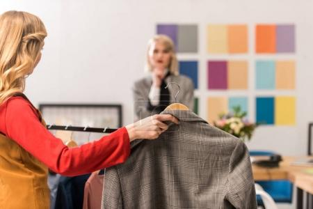 stylish magazine editors working with clothes in modern office