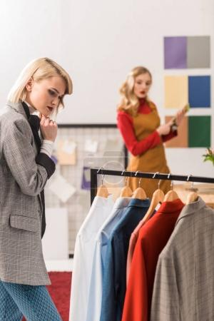 fashionable magazine editor working with clothes in modern office