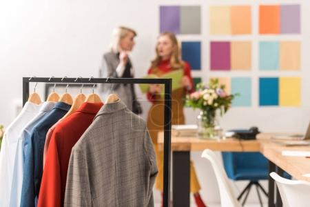 fashionable dressmakers working in modern office with clothes on foreground