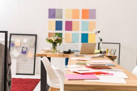Photo pour Documents sur le lieu de travail dans un bureau moderne à la mode avec palette de couleurs sur le mur - image libre de droit