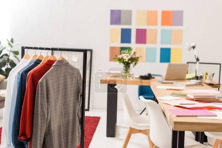 Photo pour Vêtements à la mode sur des cintres, paperasserie sur table bureau moderne avec la palette de couleurs sur le mur - image libre de droit