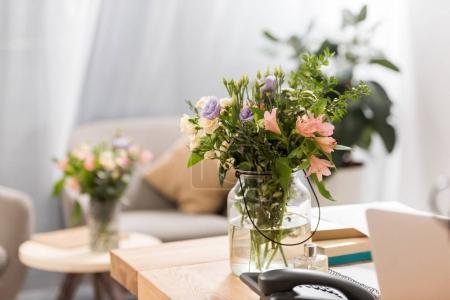 Photo pour Fleurs dans un vase sur lieu de travail dans le bureau moderne - image libre de droit