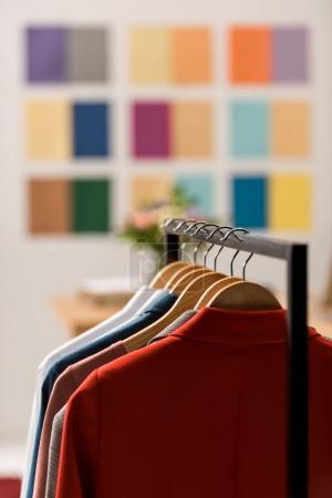 Photo for Fashionable clothes on hangers in modern office - Royalty Free Image