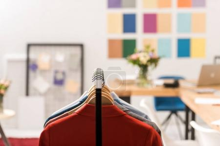 selective focus of fashionable clothes on hangers in modern office