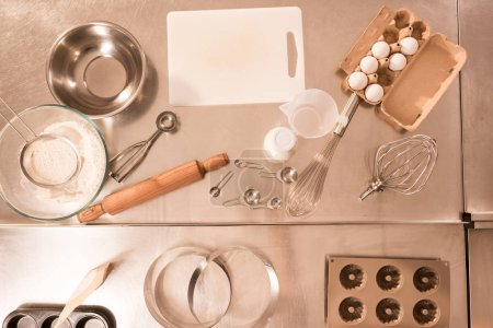 top view of ingredients for dough and kitchen utensils on counter in restaurant