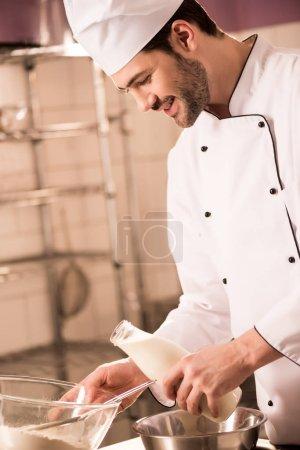 confectioner in chef hat with milk in hand making dough in restaurant kitchen